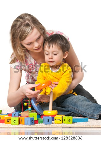 Mother and son playing on the floor with toys; on the white background - stock photo