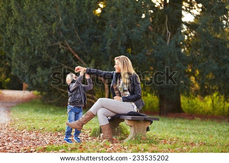 Mother and son playing together in the autumn park