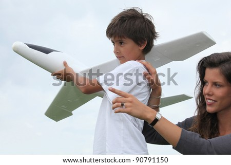 Mother and son playing with a large model toy aeroplane - stock photo
