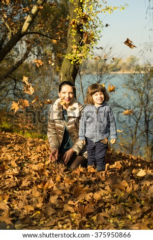 Mother and son playing with autumn leaves in park  - stock photo