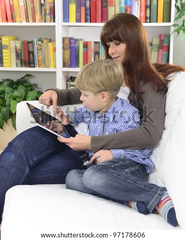 mother and son playing with digital tablet at home - stock photo