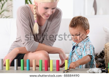 Mother and son playing with domino's - stock photo
