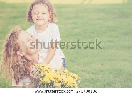 Mother and son playing with flowers on the grass at the day time. Concept of friendly family. - stock photo