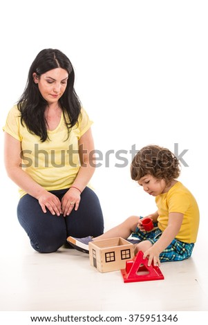Mother and son playing with toy house in their home - stock photo