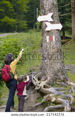 Mother and son pointing to some direction signs in the forest - stock photo