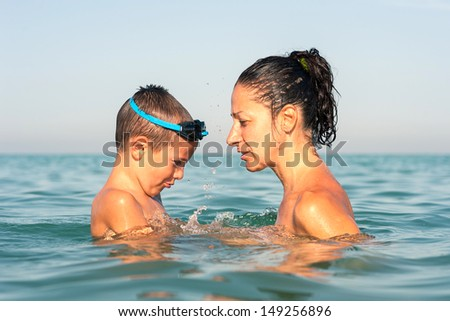 Mother and son portrait in the water at the beach.