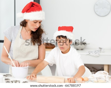 Mother and son preparing Christmas biscuits together in the kitchen - stock photo