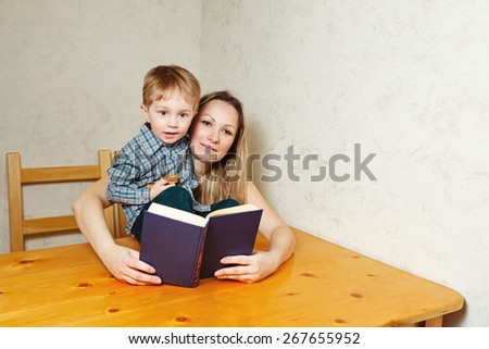 Mother and son reading a book. Mother holding a book hugging son sitting on the kitchen table. Happy family leisure. - stock photo