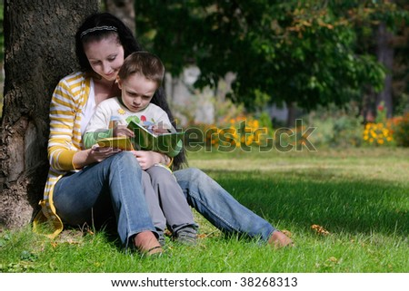 mother and son reading book in autumn park - stock photo