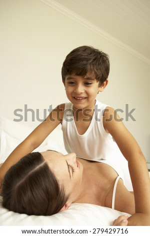 Mother And Son Relaxing On Bed - stock photo