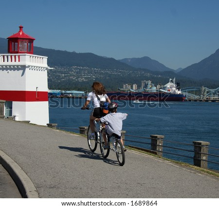 Mother and son riding the Stanley park seawall - stock photo