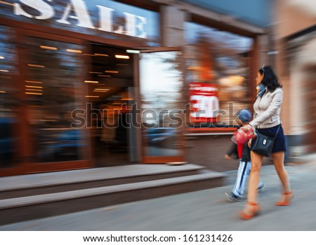 Mother and son shopping in mall. Intentional motion blur - stock photo
