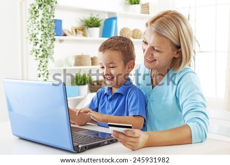 Mother and son shopping together on the interenet - stock photo