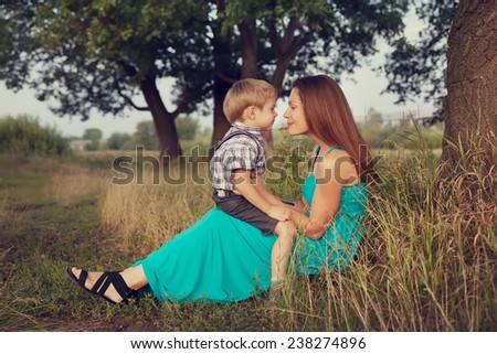 mother and son sitting face to face outdoors - stock photo