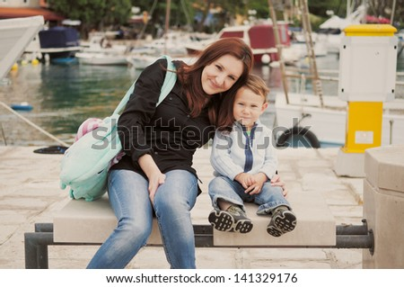 Mother and son sitting in harbor - stock photo