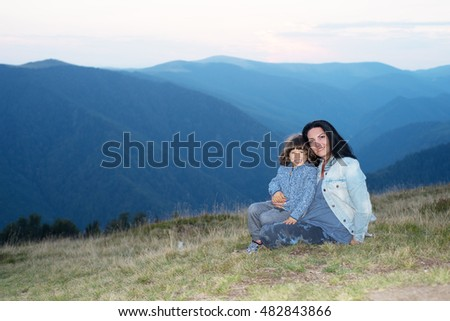 Mother and son sitting on grass at high altitude in the mountains at sunset