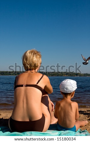 Mother and son sitting on the river beach - stock photo
