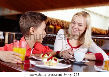 Mother and son spending time together eating delicious desserts - stock photo
