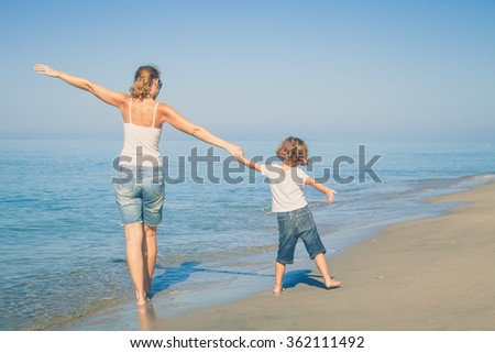 Mother and son standing on the beach at the day time. Concept of friendly family.