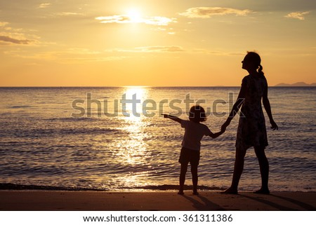 Mother and son standing on the beach at the sunset time. Concept of friendly family. - stock photo