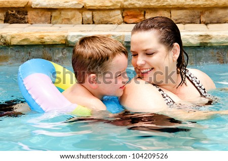 Mother and son swimming together while on vacation - stock photo