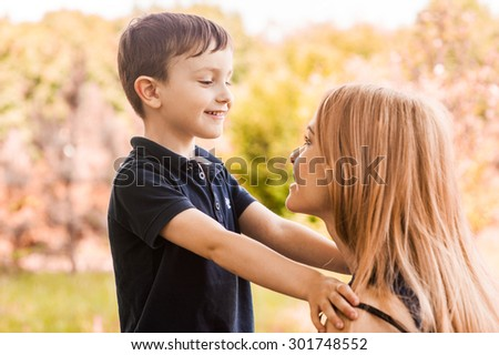 Mother and son together outdoors ponder the thought of the child and his desire - stock photo