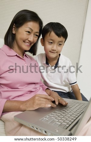 Mother and Son Using Laptop in living room - stock photo