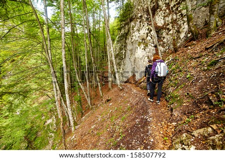 Mother and son walking on a hike trail in a forest - stock photo