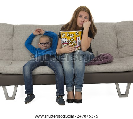 Mother and son watching a boring movie on a sofa while eating popcorn against a white background - stock photo