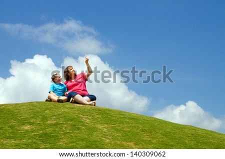 Mother and son watching clouds from grassy hill - stock photo