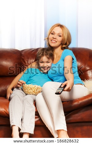 Mother and son watching television with popcorn - stock photo