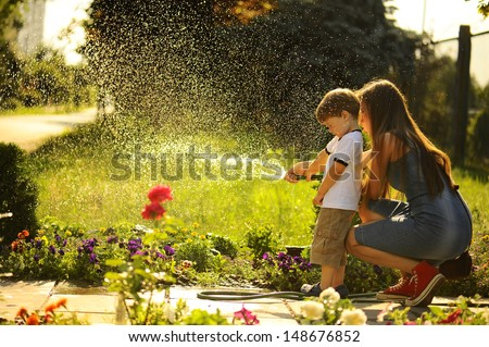 mother and son watering the lawn. - stock photo