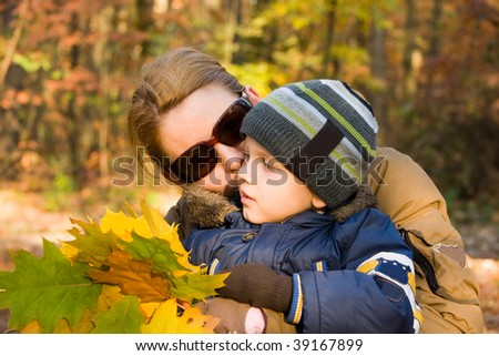 Mother and son whispering in autumn forest - stock photo
