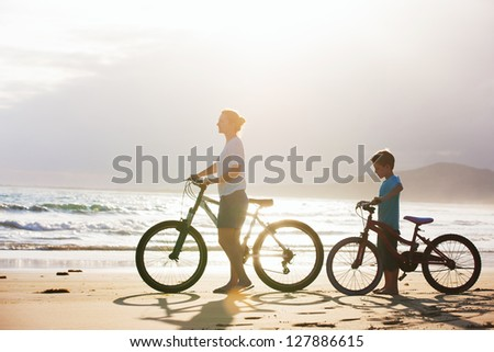 Mother and son with bikes on a beach at sunset