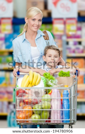 Mother and son with cart full of products in store. Concept of healthy food and consumerism
