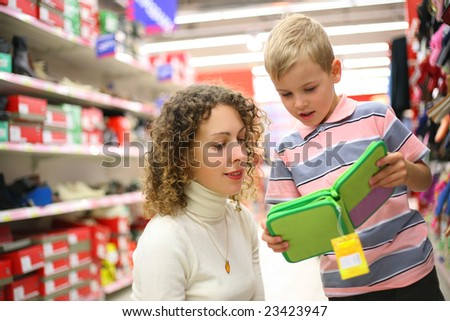 Mother and son with green box in shop - stock photo