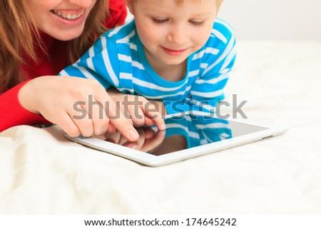mother and son with tablet at home - stock photo