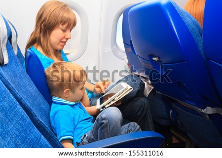 mother and son with touch pad in plane, family travel