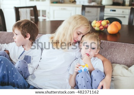 mother and sons are sitting on the couch in the kitchen