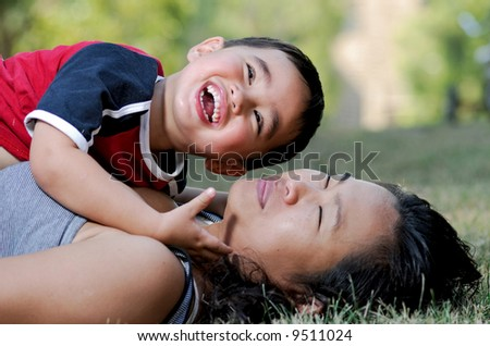 Mother and sun on grass - stock photo