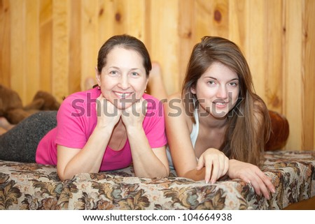 Mother and teen daughter laying on sofa at home