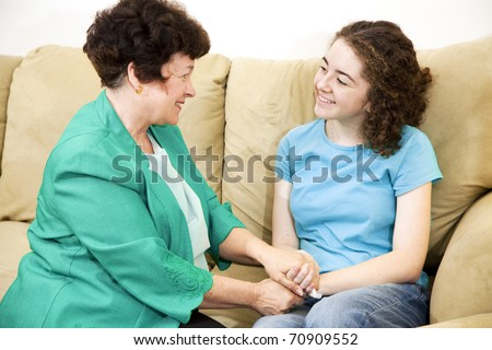 Mother and teenage daughter having a conversation together on the couch.