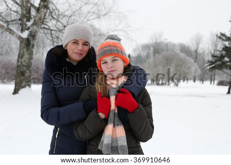 Mother and teenage daughter stand embracing in winter park on natural snowy background outdoor - stock photo