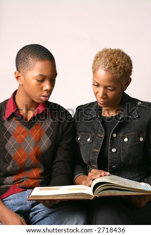 Mother and teenage son review school assignment in open book