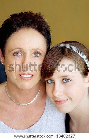 Mother and teenager daughter on yellow background