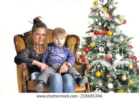 Mother and their small child sits on chair near Christmas tree - stock photo