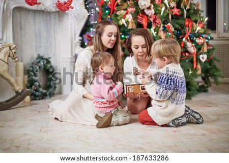 Mother and three children sits under Christmas tree around gingerbread in mother hands - stock photo