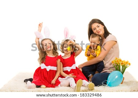 Mother and three kids prepare for Easter holiday  and sitting together on carpet - stock photo