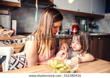 mother and toddler daughter eating grapes for breakfast at home - stock photo