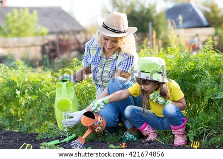 Mother and toddler daughter gardening and watering